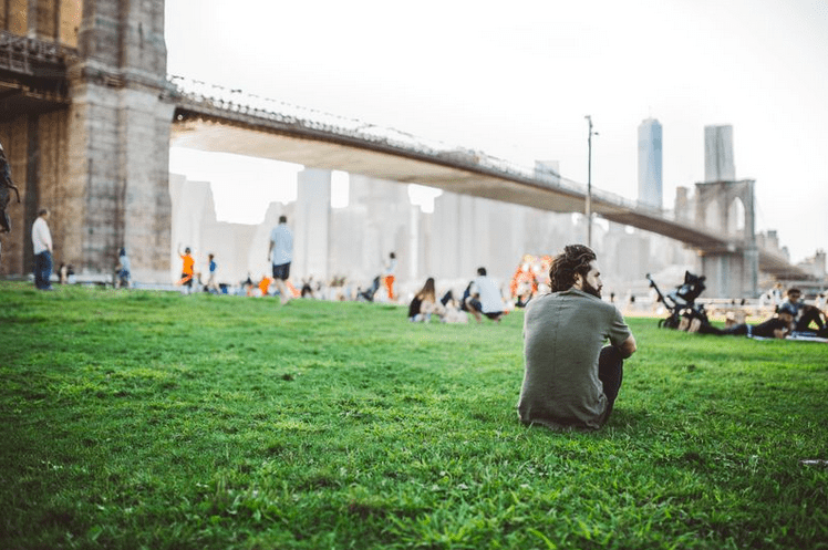 a man sitting on a green lawn below the golden gate bridge thinking of his life purpose.