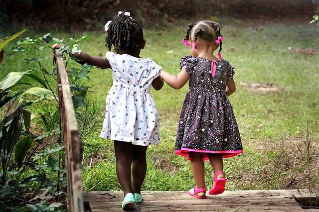 two little girls crossing a bridge holding hands
